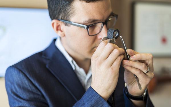jeweler examining diamond with loupe